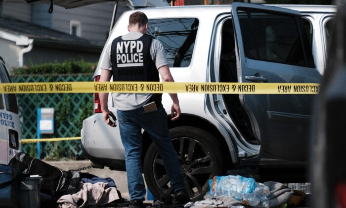 Police search a car following a stand-off in front of the 45th Police Precinct in the Bronx in New York City on July 8, 2021. (Spencer Platt/Getty Images)