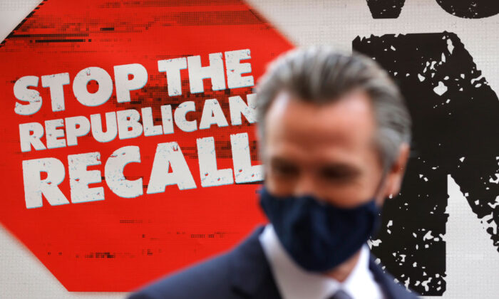 A sign against the recall is posted behind California Gov. Gavin Newsom as he talks with volunteers in San Francisco, on Aug. 13, 2021. (Justin Sullivan/Getty Images)