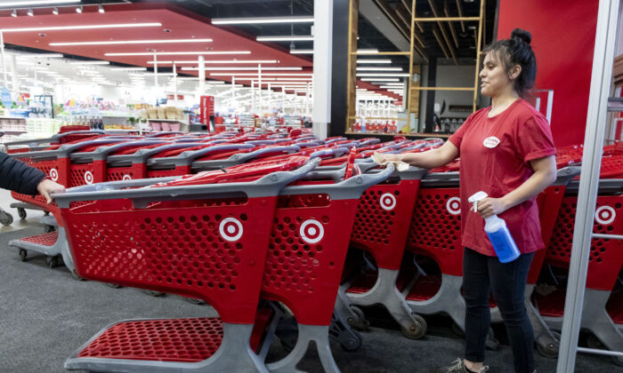 An employee sanitizes shopping carts at the entrance of a Target in Chicago's Logan Square neighborhood, on March 29, 2020. (Brian Cassella/Chicago Tribune/TNS)