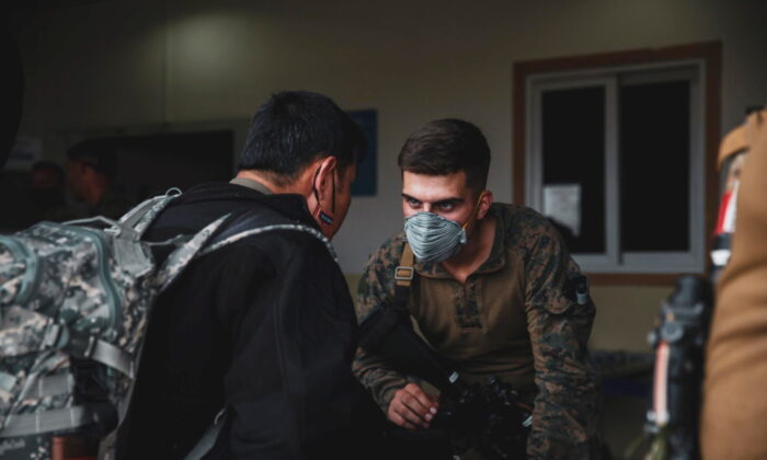 A Marine assigned to the 24th Marine Expeditionary Unit (MEU) processes an evacuee at Hamid Karzai International Airport, Kabul, Afghanistan, on Aug. 15, 2021. (U.S NAVY/Central Command Public Affairs/Sgt. Isaiah Campbell/Handout via Reuters)