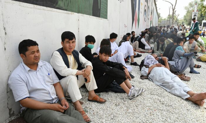 People sit near the French embassy in Kabul on Aug. 18, 2021. (Wakil Kohsar/AFP via Getty Images)
