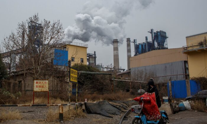 A woman rides a scooter past a steel plant in Anyang, Henan province, China, on Feb. 18, 2019. (Thomas Peter/Reuters)