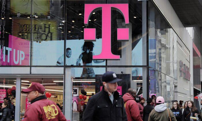 Pedestrians walk past a T-Mobile store in New York on April 27, 2018. (Lucas Jackson/Reuters)