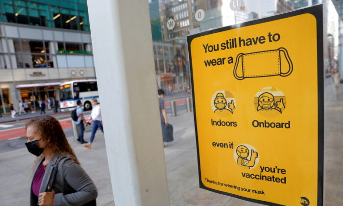A poster alerting people to wear a mask is seen on a 42nd Street subway entrance in New York City, on Aug. 2, 2021. (Andrew Kelly/Reuters)