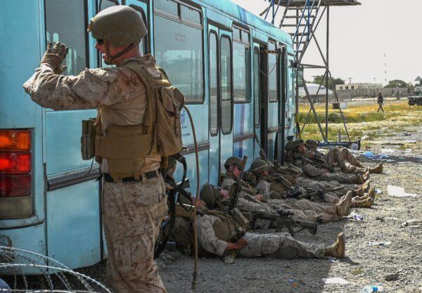 U.S. soldiers rest as Afghan people wait to leave
