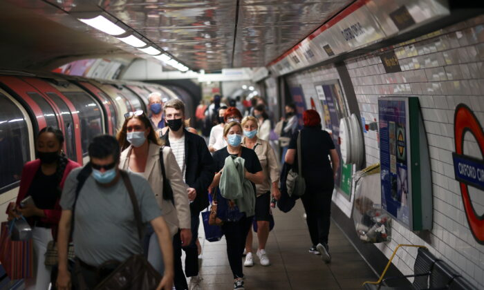 People, some wearing protective face masks, walk along a platform at Oxford Circus underground station, amid the COVID-19 pandemic, in London, on July 4, 2021. (Henry Nicholls/Reuters)