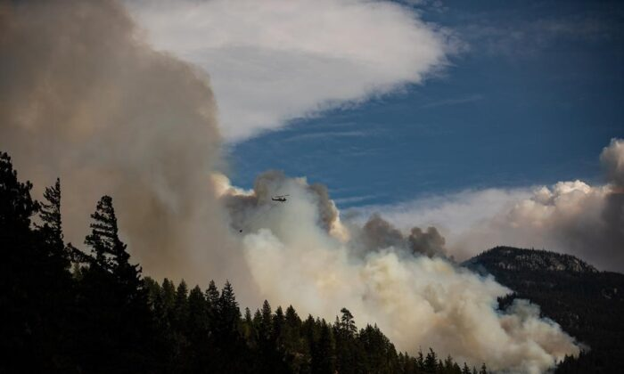 A helicopter carrying a water bucket flies past the Lytton Creek wildfire burning in the mountains near Lytton, B.C., on August 15, 2021. (The Canadian Press/Darryl Dyck)