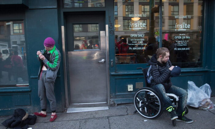 A woman prepares to inject herself with an unknown substance as a man sits in a wheelchair outside the Insite supervised consumption facility in Vancouver's Downtown Eastside on Feb. 21, 2017. (The Canadian Press/Darryl Dyck)