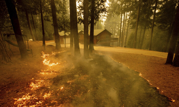 Flames from the Caldor Fire scorch the ground near a structure in Grizzly Flats, Calif., on  Aug. 18, 2021. (Ethan Swope/AP Photo)