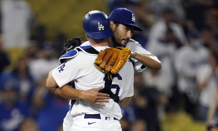 Los Angeles Dodgers relief pitcher Mitch White, right, hugs catcher Will Smith after the team's 9-0 win over the Pittsburgh Pirates in a baseball game in Los Angeles on Aug. 18, 2021. (AP Photo/Marcio Jose Sanchez)