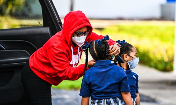 A mother adjusts the protective mask on her child as she enters the St. Lawrence Catholic School on the first day of school after summer vacation in north of Miami, on Aug. 18, 2021. (Chandan Khanna/AFP via Getty Images)