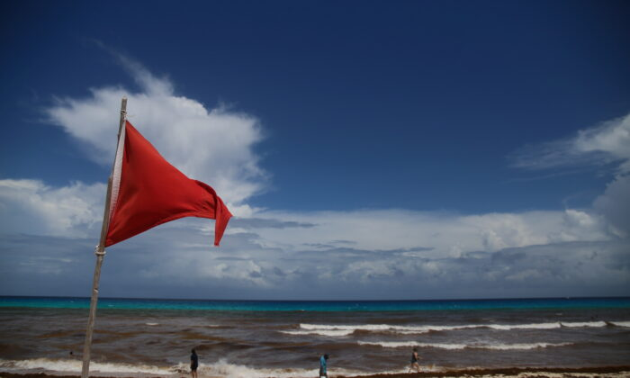 A red flag on the beach warns beachgoers of hazards due to the proximity of Hurricane Grace in Cancun, Mexico, on Aug. 18, 2021. (Paola Chiomante/Reuters)