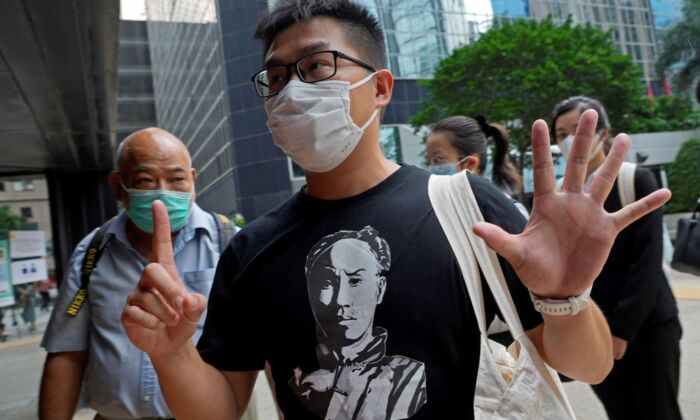 """Pro-democracy activist Raphael Wong gestures, signifying the """"Five demands, not one less,"""" outside a local court in Hong Kong on Aug. 19, 2021. (Vincent Yu/AP Photo)"""