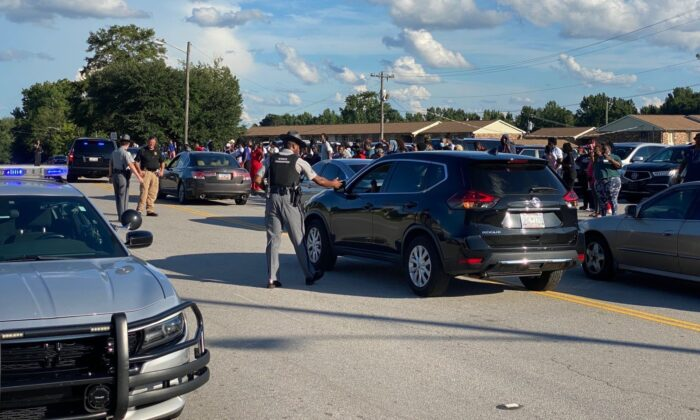 Parents wait for students to be released after a shooting outside Orangeburg-Wilkinson High School in Orangeburg, South Carolina, on Aug. 18, 2021. (Gene Crider/The Times and Democrat via AP)