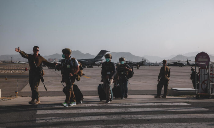 A Marine assigned to the 24th Marine Expeditionary Unit escorts Department of State personnel to be processed for evacuation at Hamid Karzai International Airport, in Kabul, Afghanistan on Aug. 15, 2021. (Sgt. Isaiah Campbell/U.S. Marine Corps via AP)