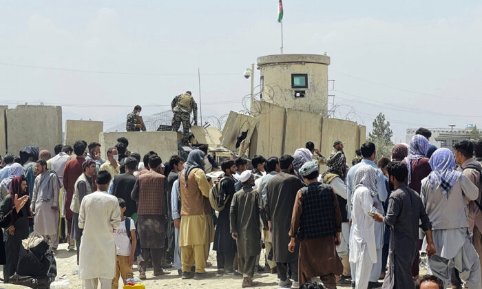 Afghan security guards stand on a wall as hundreds of people gather outside the international airport in Kabul, Afghanistan, on Aug. 17, 2021. (AP Photo)