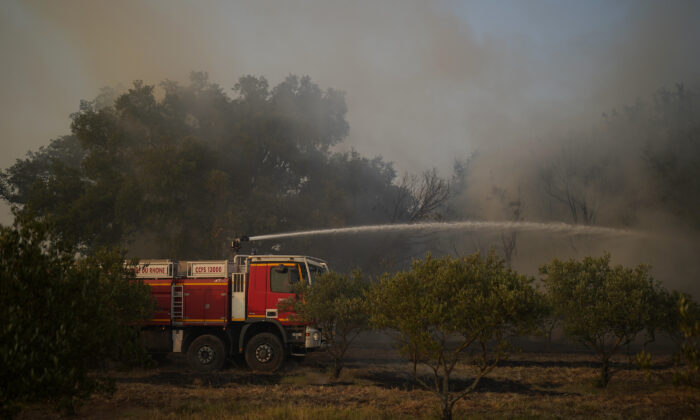 A fire brigade truck hoses a fire next to save olive trees near Le Luc, southern France, on Aug. 18, 2021. (Daniel Cole/AP Photo)