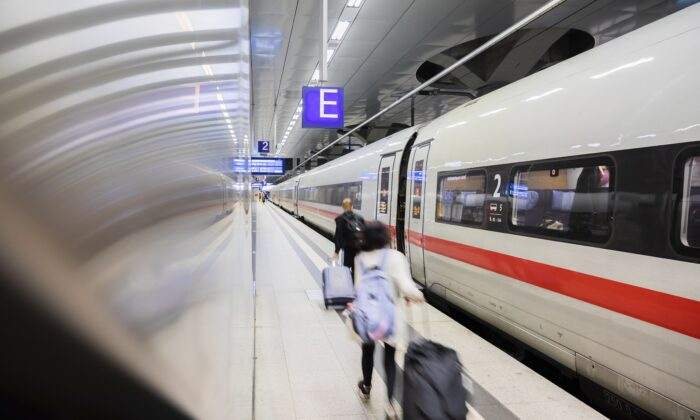 Passengers walk along an ICE train at Berlin Central Station in Berlin, Germany, on Aug. 20, 2021. (Christoph Soeder/dpa via AP)