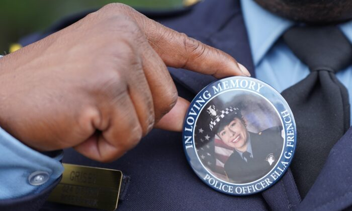 Chicago police officer Timothy Grisby holds up a pin button bearing the image of slain officer Ella French outside St. Rita of Cascia Church in Chicago, IL on Aug. 19, 2021. (Cara Ding/The Epoch Times)