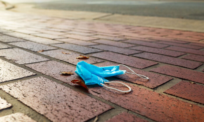 A face mask lies discarded on the ground in Orange, Calif., on June 22, 2020. (John Fredricks/The Epoch Times)