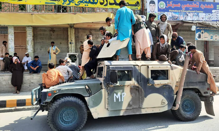 Taliban fighters and local residents sit on an U.S. provided Afghan National Army Humvee vehicle along the roadside in Laghman province on Aug. 15, 2021. (AFP via Getty Images)