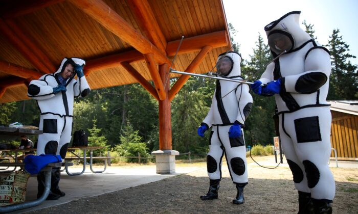 Austin Johnson (L), Jake Bodart (C) and Jessica Rendon (R) of the Oregon Department of Agriculture look at the advanced telemetry system used for tracking while wearing hornet extraction suits, during an Asian giant hornet field training day held by the Washington State Department of Agriculture Pest Program, at Birch Bay State Park near Blaine, Wash., on Aug. 18, 2021. (Lindsey Wasson/Reuters)