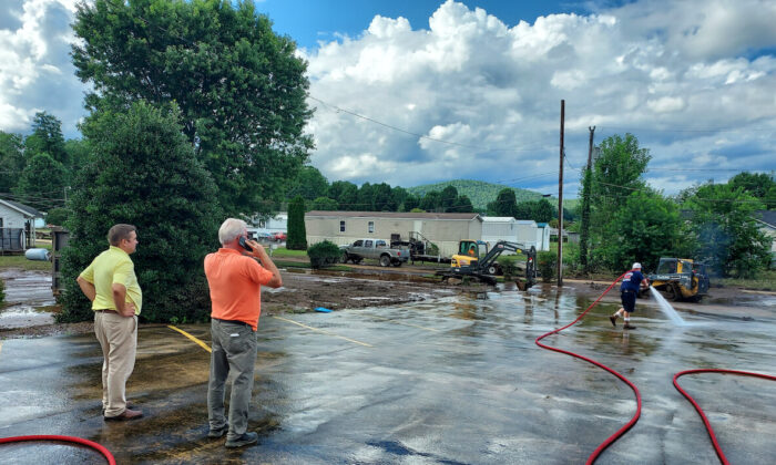 Anchor Baptist Church Pastor Randy Barton and Lowe's Home Improvement Store Manager Brent McCrimmon survey the damage after Tropical Depression Fred flooded  the Davidson River Valley in Transylvania County on Aug. 18, 2021. (Matt McGregor/The Epoch Times)