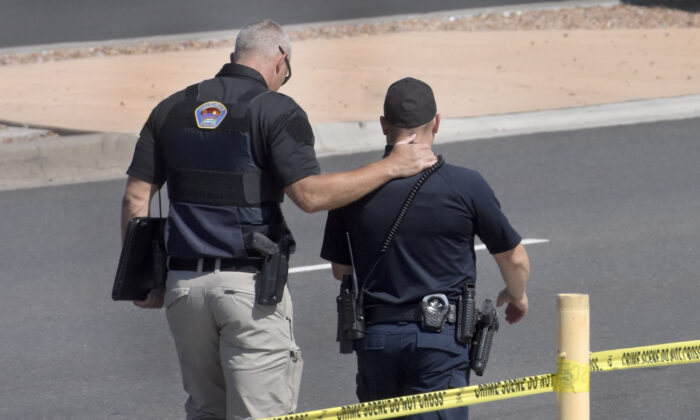 Two officers walk away from the scene after a shootout that left multiple officers injured in northeast Albuquerque, N.M., on Aug. 19, 2021. (Robert Browman/The Albuquerque Journal via AP)