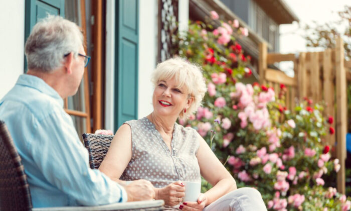 Senior couple enjoying their coffee sitting on porch in front of their house