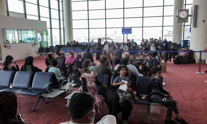 Evacuees from Afghanistan sit in a hall upon their arrival at Al Maktoum International Airport in the United Arab Emirates, on Aug. 19, 2021. (Giuseppe Cacace/AFP via Getty Images)