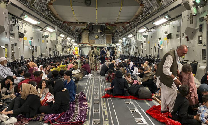 Afghan people sit inside a U.S. military aircraft to leave Afghanistan at the military airport in Kabul on Aug. 19, 2021 after the Taliban's takeover of Afghanistan. (Shakib Rahmani/AFP via Getty Images)