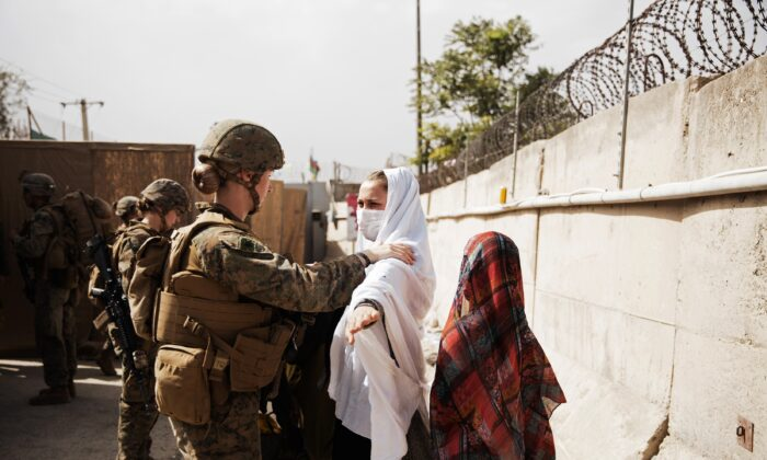 Two civilians during processing through an Evacuee Control Checkpoint during an evacuation at Hamid Karzai International Airport, in Kabul, Afghanistan on Aug. 18, 2021. (Staff Sgt. Victor Mancilla/U.S. Marine Corps via AP)