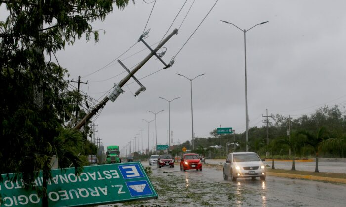 A road sign brought down by the winds of Hurricane Grace lays on the side of the highway in Tulum, Quintana Roo state, Mexico, on Aug.19, 2021. (Marco Ugarte/AP Photo)