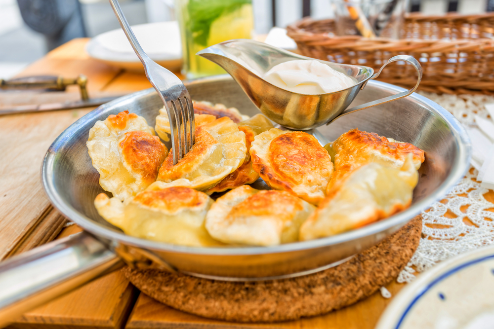 Homemade,Polish,Pierogis,With,Sour,Cream,And,Parsley,On,Table