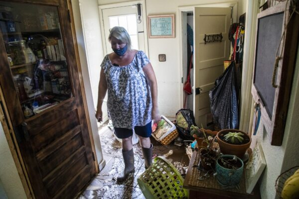 womna-looks-over-damaged-home