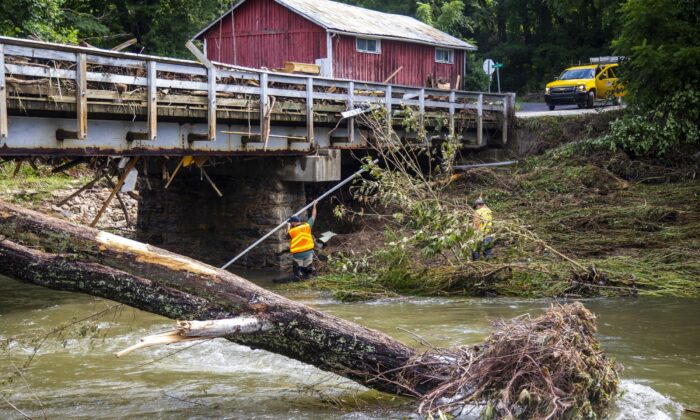 NCDOT workers assess damage to a bridge spanning the Pigeon River, in Bethel, N.C., on Aug. 19, 2021. (Travis Long/The News & Observer via AP)