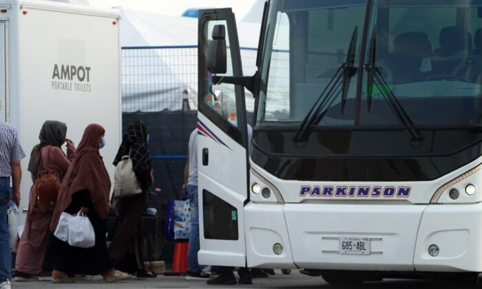 Refugees from Afghanistan and Canadian Citizens board a bus after being processed at Pearson Airport in Toronto, on Aug 17, 2021, after arriving indirectly from Afghanistan. (The Canadian Press/Sean Kilpatrick)