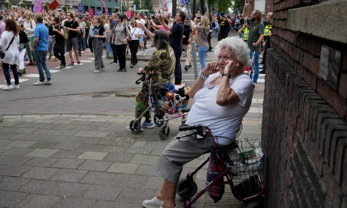 An older woman shields her ears during a protest of organizers and fans of music festivals stage against the government's COVID-19 restrictions on large-scale outdoor events, in Amsterdam, Netherlands, on Aug. 21, 2021. (Peter Dejong /AP Photo)