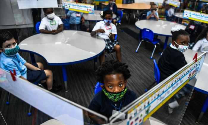 Student wear facemasks as they attend their first day in school after summer vacation at the St. Lawrence Catholic School  in north of Miami on Aug. 18, 2021. (Photo by CHANDAN KHANNA / AFP) (Photo by CHANDAN KHANNA/AFP via Getty Images)