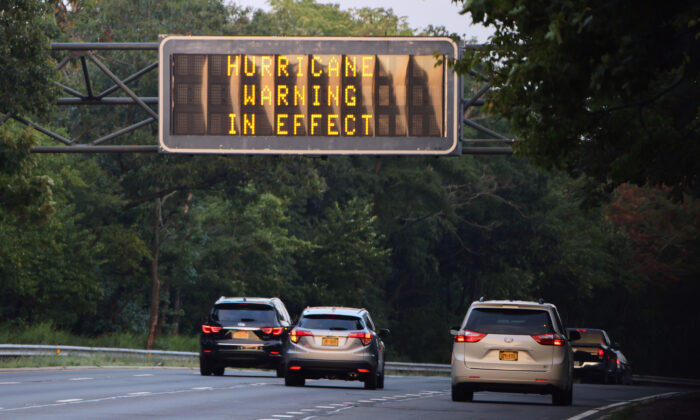 """A sign on the Southern Parkway alerts drivers that there is a """"Hurricane Warning in Effect"""" as Hurricane Henri moves up the coast in Wantagh, N.Y., on Aug. 21, 2021. (Bruce Bennett/Getty Images)"""