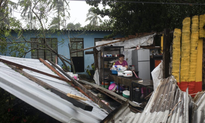 A woman begins clearing debris from her kitchen after a part of her home was damaged by winds brought on by Hurricane Grace, in Tecolutla, Veracruz State, Mexico, Saturday on Aug. 21, 2021. (Felix Marquez/AP Photo)