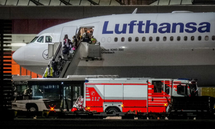 People disembark from a Lufthansa aircraft coming from Tashkent in Uzbekistan that landed at the airport in Frankfurt, Germany, on Aug. 18, 2021. On board were about 130 people that were evacuated from Afghanistan. (Michael Probst /AP Photo)