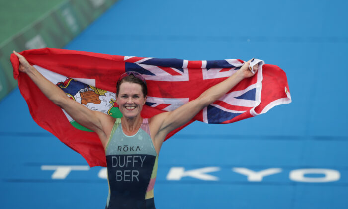 Flora Duffy of Bermuda holds the national flag as she celebrates victory during the women's individual triathlon competition at the Tokyo 2020 Olympic Games at the Odaiba Marine Park in Tokyo, Japan, on July 27, 2021. (Hannah Mckay/Reuters)