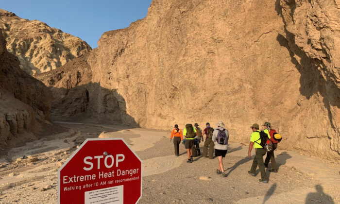 """An inter-agency search and rescue crew walks past a sign reading"""" """"Stop, Extreme Heat Danger,"""" with park rangers responding on foot near Red Cathedral along the Golden Canyon Trail in Death Valley National Park, Calif., on Aug. 18, 2021. (National Park Service via AP)"""