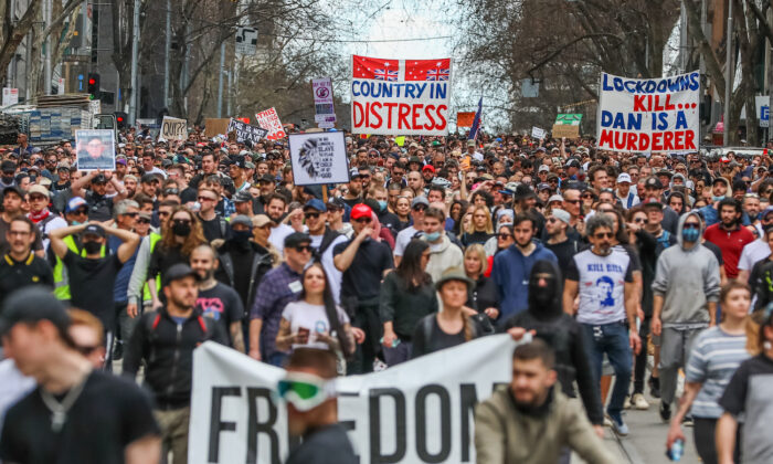 Protesters are seen marching holding banners in Melbourne, Australia, on on Aug, 21, 2021. (Getty Images)