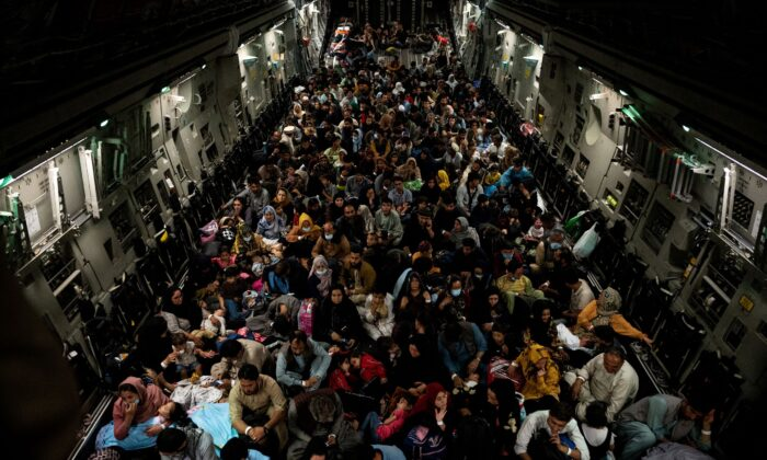 Evacuees from Afghanistan sit inside a military aircraft during an evacuation from Kabul, in this photo at undisclosed location on Aug. 19, 2021. (Staff Sgt. Brandon Cribelar/U.S. Marine Corps/Handout via Reuters)