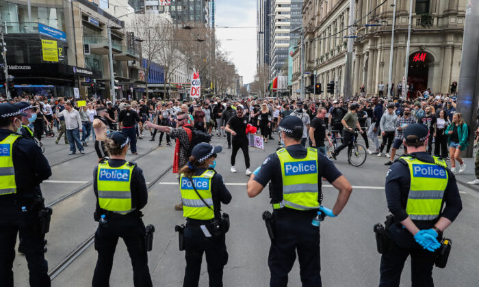 Protesters shout and gesture towards police officers in Melbourne, Australia, on Aug. 21, 2021. (Getty Images)