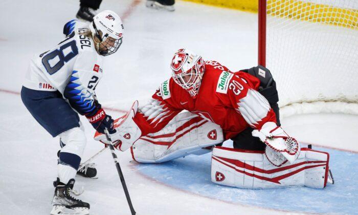 Switzerland goalie Andrea Braendli (R) blocks the net on United States' Amanda Kessel during the second period of an IIHF women's hockey championships game in Calgary, Alberta, on Aug. 20, 2021. (Jeff McIntosh/The Canadian Press via AP)