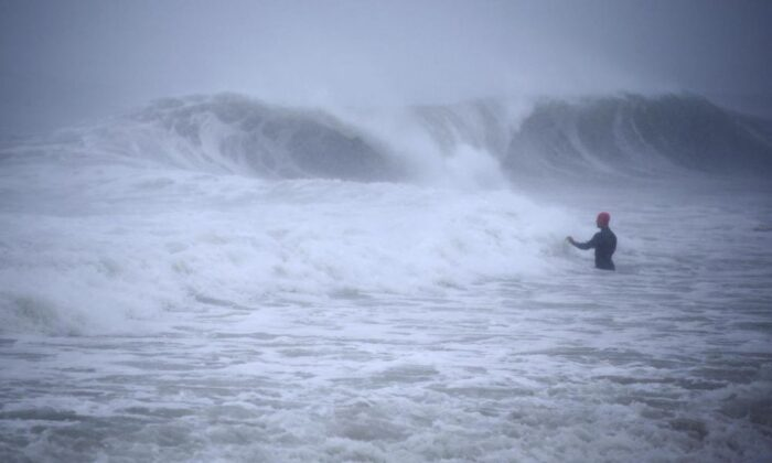 Matt Prue, from Stonington, Conn., walks out into the Atlantic Ocean to body surf the waves from Tropical Storm Henri as it approaches Westerly, R.I., on Aug. 22, 2021. (Stew Milne/AP Photo)