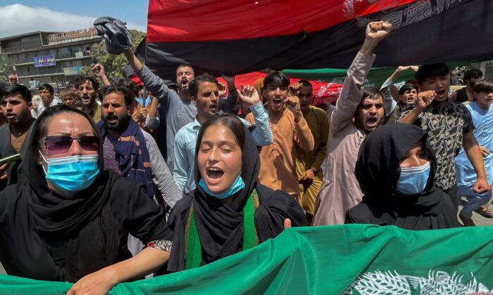 People carry the national flag at a protest held during the Afghan Independence Day in Kabul, Afghanistan, on Aug. 19, 2021. (Stringer/Reuters)